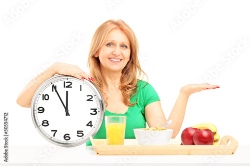 Mature woman with wall clock and fruit and vegetables in a woode