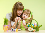 mother and child girl paint easter eggs over green background