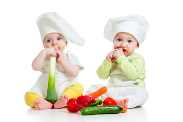 babies boy and girl wearing a chef hat with healthy  food vegeta