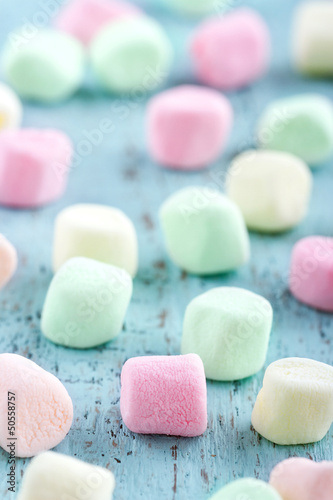 Colorful small marshmallows on wooden background