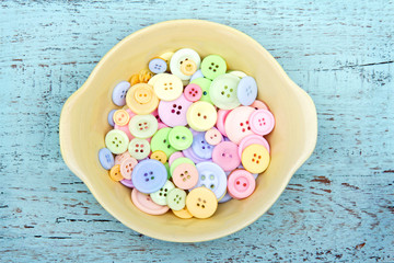 Pastel color buttons in a yellow bowl