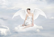 Beautiful young woman as angel sitting on a cloud
