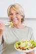 Smiling mature woman eating salad