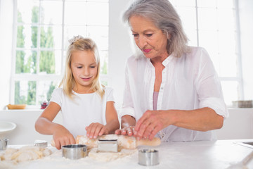 Grandmother and granddaughter making biscuits