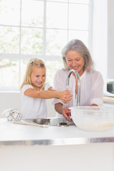 Happy grandmother and granddaughter washing hands
