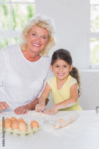 Granddaughter and grandmother preparing biscuits together