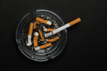 Burning cigarette left in ashtray