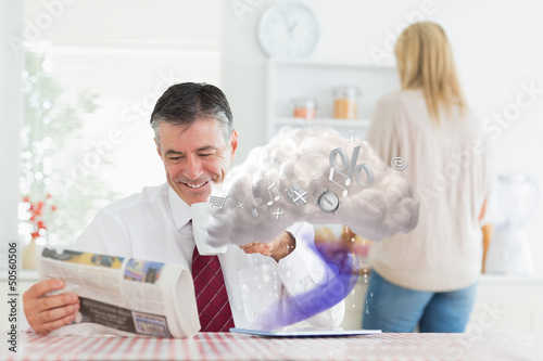 Businessman reading paper while tablet is connecting to cloud co