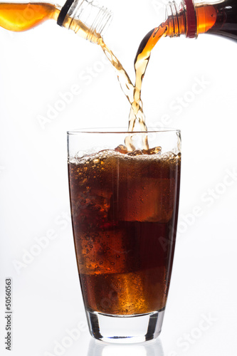 Soda and alcohol filling a glass with ice cube