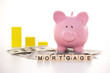 Piggy bank beside graph and mortgage spelled out in plastic lett