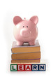 Piggy bank standing on stack of books with learn spelled out in