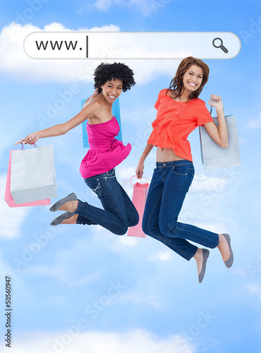 Happy girls jumping with their shopping bags under address bar