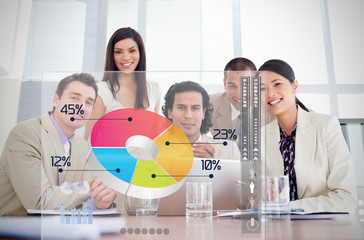 Smiling business workers looking at colorful pie chart interface
