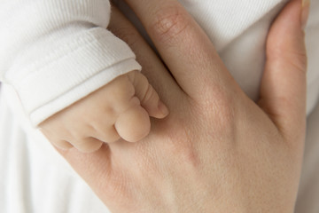 Eine junge Mutter hält zärtlich die kleine Hand ihres Säuglings