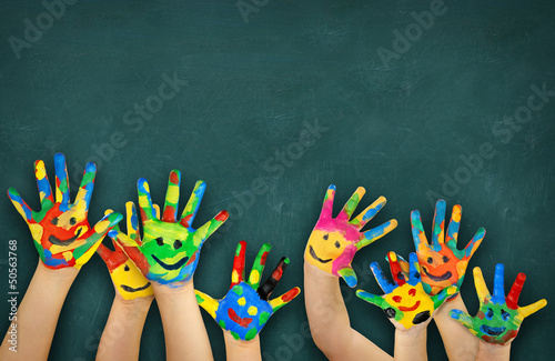 Leinwanddruck Bild bunte Kinderhände vor Schultafel