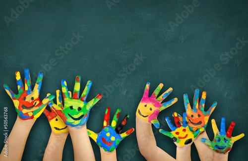 Leinwandbild Motiv bunte Kinderhände vor Schultafel