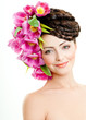 model with large hairstyle and flowers in her hair.