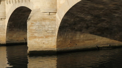 Detail of two Pont Neuf arches in morning sun in Paris, France.