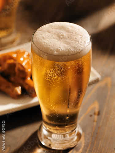 tall glass of beer with foamy head