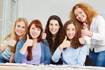 Erfolgreiche junge Frauen halten Daumen hoch