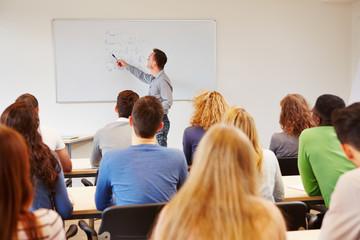 Schüler hören Lehrer an Tafel zu
