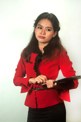 Asian woman wearing red suit posing holding a clipboard .