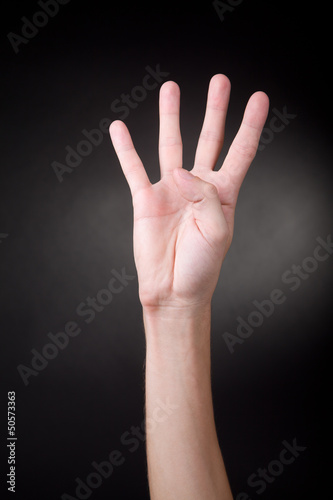 Human hand showing four fingers.