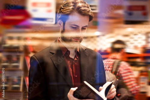 Forty years old man reading a book inside bookstore