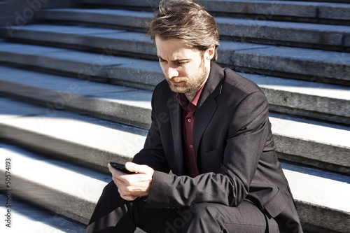 Businessman outside office looking on a mobile phone