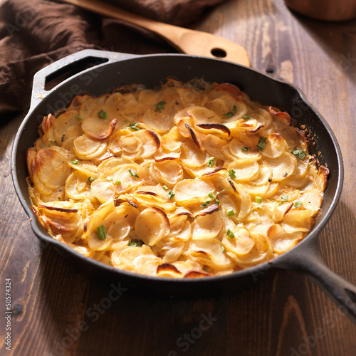 scalloped potatoes in rustic iron skillet