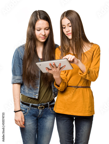 Teen girls sharing a tablet computer.