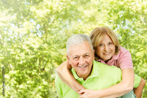 happy senior man giving piggyback ride