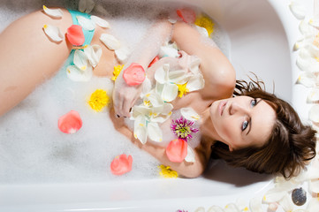Beautiful lady taking a bath with flower petals