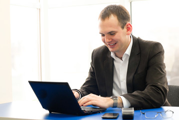 Happy businessman using laptop in building, smiling.