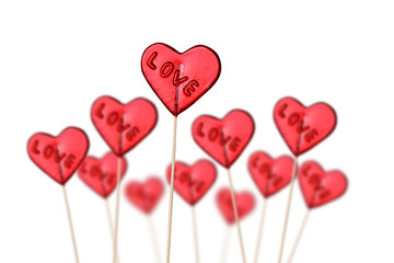 Red heart shaped lollipops on white background.