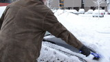 man hand clean remove snow car windshield window brush winter