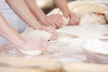 zwei bäcker kneten teig
