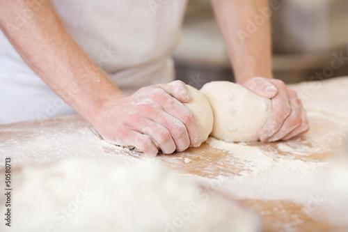 bäcker knetet brotteig - 50580713