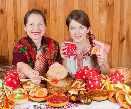 Women  eating pancake with caviare