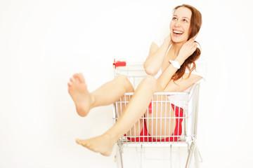 junge Frau im Einkauswagen