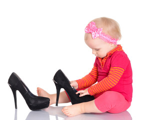 Cute little baby girl trying on her mother's shoes on white back