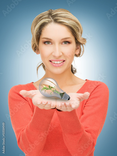 woman showing green light bulb