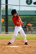 Youth baseball player swinging bat