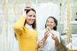 saleswoman helps bride chooses bridal diadem