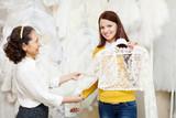 bride chooses bridal clothes at shop of wedding fashion
