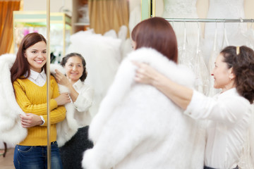 Female shop consultant helps girl chooses fur cape at shop