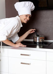 female chef in whte uniform cooking in kitchen