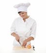 female cook in whte uniform cutting onion