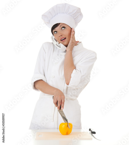 surprised female cook cutting paprika and speaking on the phone