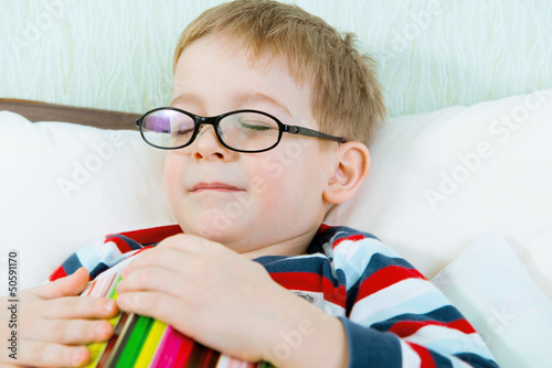Little tired boy sleeping with book in bed
